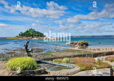 21 June 2018: Marazion, Cornwall, UK - St Michael's Mount from Marazion, with a dolphin fountain in the forground. People can be seen making their way - Stock Image