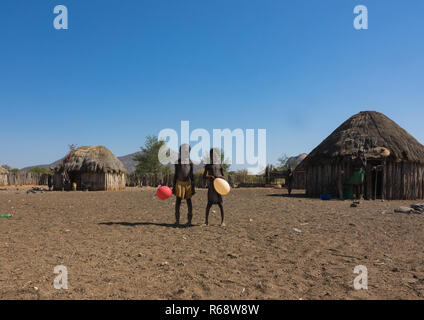 Young Muhakaona kids playing with a balloon in the middle of their village, Cunene Province, Oncocua, Angola - Stock Image