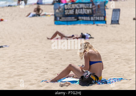 Bournemouth, UK. 6th July 2018. UK Weather, a young lady on the beach in Bournemouth as the summer 2018 heatwave continues. Credit: Thomas Faull / Alamy Live News - Stock Image