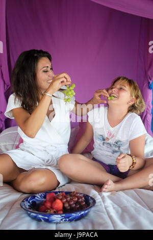 Hispanic mother and daughter having fun at eating grapes in the child's bedroom - Stock Image