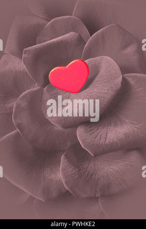Small red heart on rose flower petals. Romantic background texture for a Valentine's or Wedding day greetings card, desaturated effect. - Stock Image