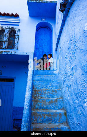 Chefchaouen, Morocco : Two children sit on top of a blue-washed staircase in the medina old town. - Stock Image