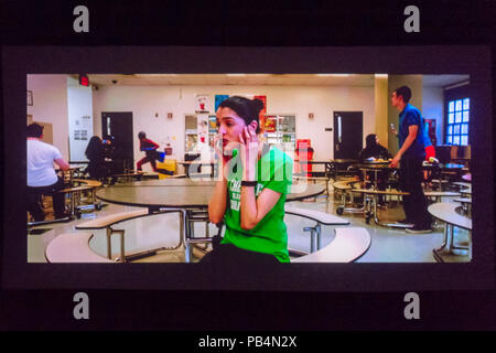 Bellmore, New York, USA. July 18, 2018. In short film The Adventures of Penny Patterson, the title character, played by actor AJNA JAI, calls Steve, her boyfriend and lab partner, who isn't helping with their science fair project. Penny didn't notice Steve was superhero behind her in high school cafeteria. The comedy, sci-fi, woman directed film was nominated for Best Student Film at LIIFE 2018, the Long Island International Film Expo. - Stock Image