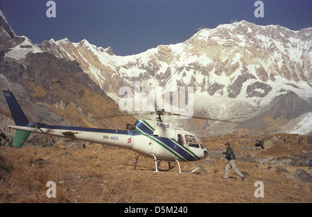 Client about to board Karnali Helicopter at Annapurna Base Camp with Annapurna I 8-091 metres Nepal Himalayas - Stock Image