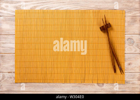 two sushi chopsticks with empty bamboo mat or wood plate on brown wooden Background Top view with copy space. empty asian food background. - Stock Image