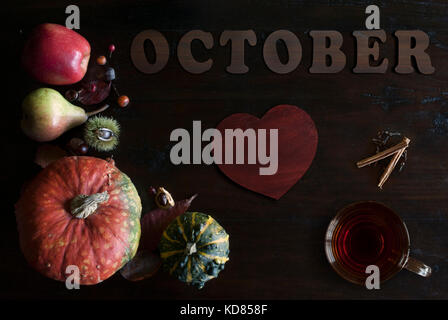 beautiful rustic fall flat lay with leaves, pumpkins, chestnuts, cup of tea and letters october on wooden background - Stock Image