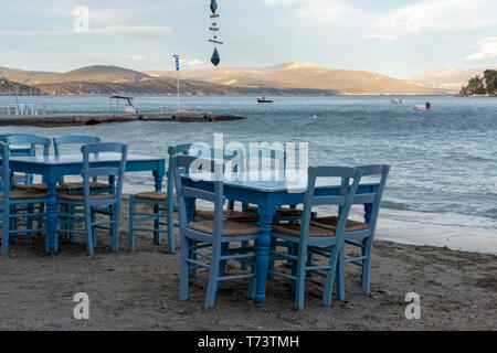 Traditional greek tavern with wooden tables on sandy beach near water waiting for tourists in Tolo, Peloponnese, Greece, vacation season is starting - Stock Image