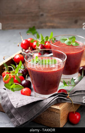 smoothies sweet cherry in a glass, fresh sweet cherry on a gray background - Stock Image