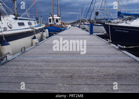 A view along a floating walkway at Lochinver harbour, Scotland with private yachts moored on either side - Stock Image