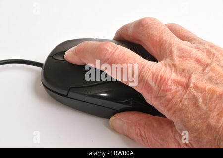 Old hand working a computer mouse. UK - Stock Image