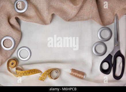 fabric for sewing curtains. cloth, scissors, measuring tape, rings on a light fabric. view from above - Stock Image