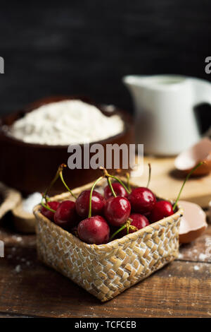 closeup of the ingredients to prepare a coca de cireres, a cherry sweet flat cake typical of Catalonia, Spain, such as wheat flour, milk, sugar, eggs  - Stock Image