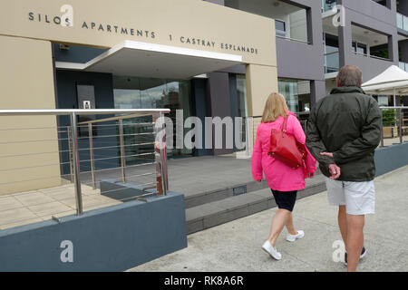 Couple walks by Silos Apartments, Castray Esplanade, near Salamanca, Hobart, Tasmania, Australia. No MR or PR - Stock Image