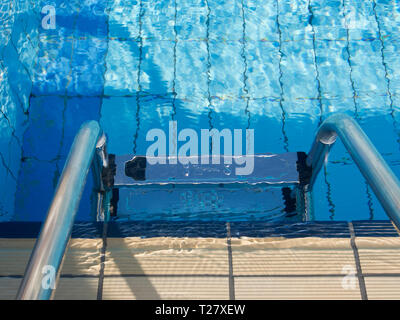 Entering a heated outdoors swimming pool in a comfortable hotel is are many holidaymakers dream of  a vacation in Cyprus in the autumn - Stock Image