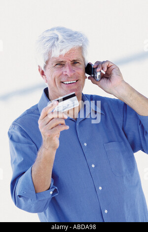 Senior man with a cell phone and a credit card - Stock Image