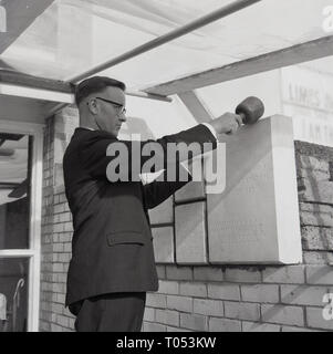 1967, 'Great is Thy Faithfulness', a man in suit,  a pastor, ceremonially laying a memorial stone or plaque in foyer of a Baptist church building, England, UK. - Stock Image