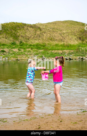 2 sisters aged 3 and 4 years old, collecting seaweed at the beach. - Stock Image
