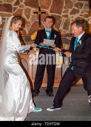 Couple tie the knot during wedding ceremony; Congressional Church; Buena Vista; Colorado; USA - Stock Image