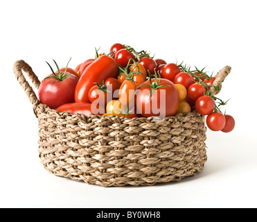 A basket with a variation of tomatoes isolated on white - Stock Image
