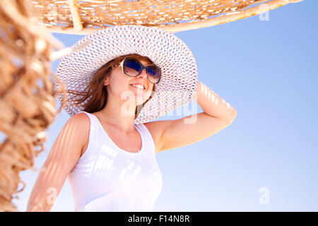 A young pretty woman in a hat on the beach - Stock Image
