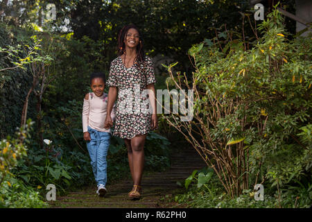 Mother and daughter holding hands walking down a garden path - Stock Image