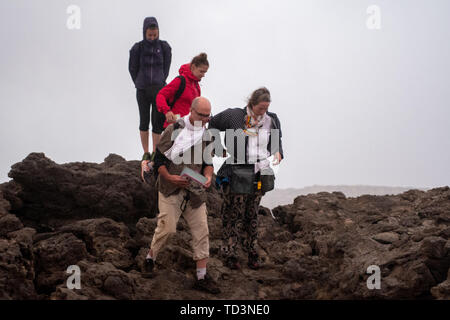 Tourists traversing the precarious terrain of the Erta Ale Volcano, a continuously active basaltic shield volcano and lava lake in the Afar Region of  - Stock Image