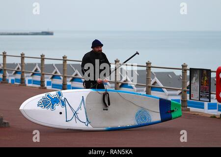 Hastings, East Sussex, UK. 05 Jan, 2019. UK Weather: A chilly start to the morning on the seafront in Hastings, East Sussex. A paddle boarder gets his equipment ready as he heads out. © Paul Lawrenson 2018, Photo Credit: Paul Lawrenson / Alamy Live News - Stock Image