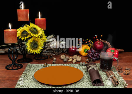 Thanksgiving setting for one with candle light, fruit, vegetables, hot tea, and sunflowers with cinnamon sticks and anise. - Stock Image