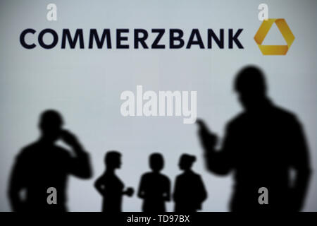 The Commerzbank logo is seen on an LED screen in the background while a silhouetted person uses a smartphone in the foreground (Editorial use only) - Stock Image
