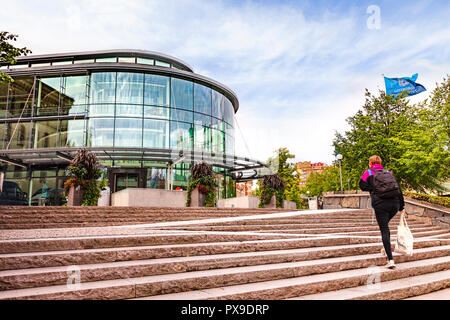 14 September 2018: Gothenburg, Sweden - Young woman carrying a bag, walking up the steps to Gothenburg University. - Stock Image
