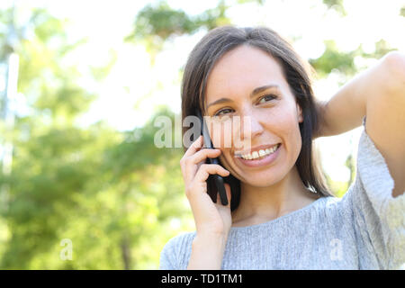Happy woman calls on smart phone standing outdoors in a park - Stock Image