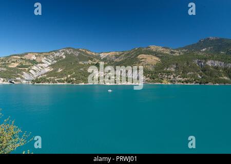 Lac de Serre-Ponçon  Lac de Serre-Ponçon is located in Hautes-AlpesLac de Serre-PonçonLac de Serre-Ponçon - Stock Image