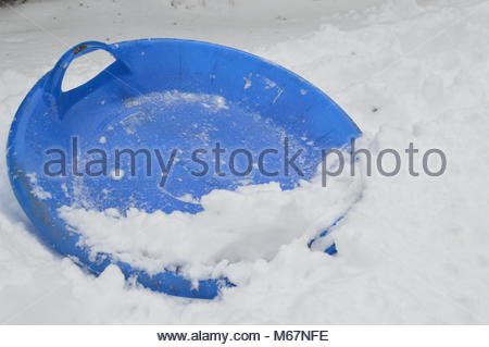 Blue plastic disc sledge in the snow. - Stock Image