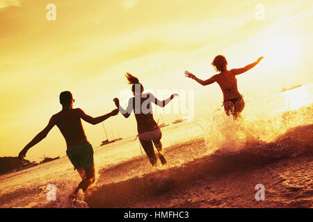 Happy friends sea sunset beach - Stock Image