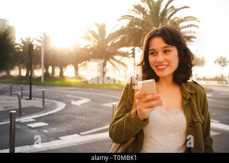 Happy young beautiful woman in green jacket talking on the phone walking on the city street at sunset - Stock Image