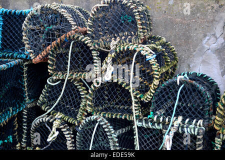Lobster or crab pots, the traps stacked beside a seawall - Stock Image