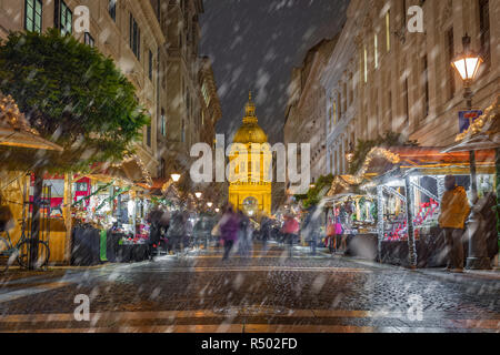 Budapest, Hungary - Snowy night at Zrinyi street with Christmas market and illuminated St.Stephen's Basilica at background - Stock Image