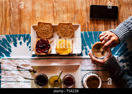 Vertical top point of view of woman doing breakfast in hotel or home - bread and mermalades and coffee time for healthy energy food to start the day - - Stock Image