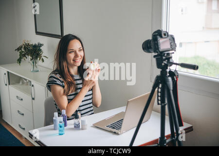 Girl videoblogger or beauty blogger records video for subscribers how to use the cream and talks about it. - Stock Image