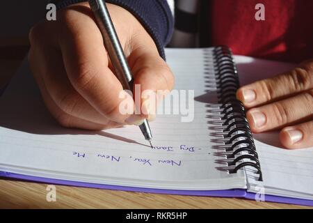 Young woman seated at a desk, writing a list of New Year resolutions in a spiral bound notebook, starting with Dry January. Midsection, close-up hand - Stock Image