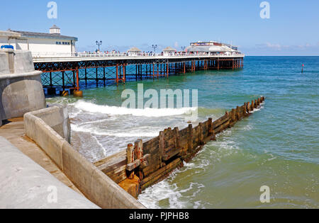 A view of the Pier from the promenade at high water at the North Norfolk seaside resort of Cromer, Norfolk, England, United Kingdom, Europe. - Stock Image