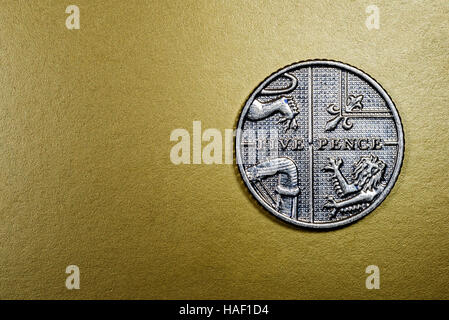 Five pence English currency coin in a macro close-up on a rich luxurious golden background. Copyspace area for finance, - Stock Image