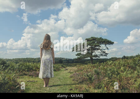 a girl in a floral dress is staning on a field with bracken - Stock Image