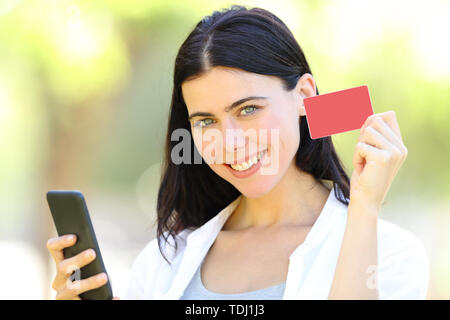 Happy adult woman showing a blank credit card holding smart phone standing in a park - Stock Image