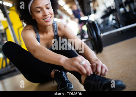 Fit sportswoman exercising and training at fitness club - Stock Image