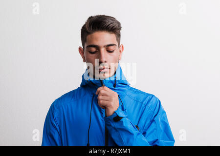 Portrait of a young serious hispanic man with blue anorak in a studio, looking down. - Stock Image
