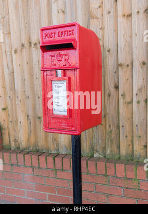red polemounted post box showing collection times by a wooden fence Wallasey Village February 2019 - Stock Image