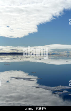 Glassy calm sea of Baffin Bay in the Arctic Circle giving a beautiful reflection of the sky, viewed from an expedition ship - Stock Image