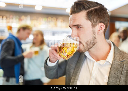 Young man is drinking a glass of beer in a pub or pub - Stock Image