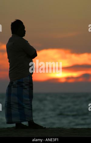 Silhouette of man and sunset over the sea Negombo beach Sri Lanka - Stock Image